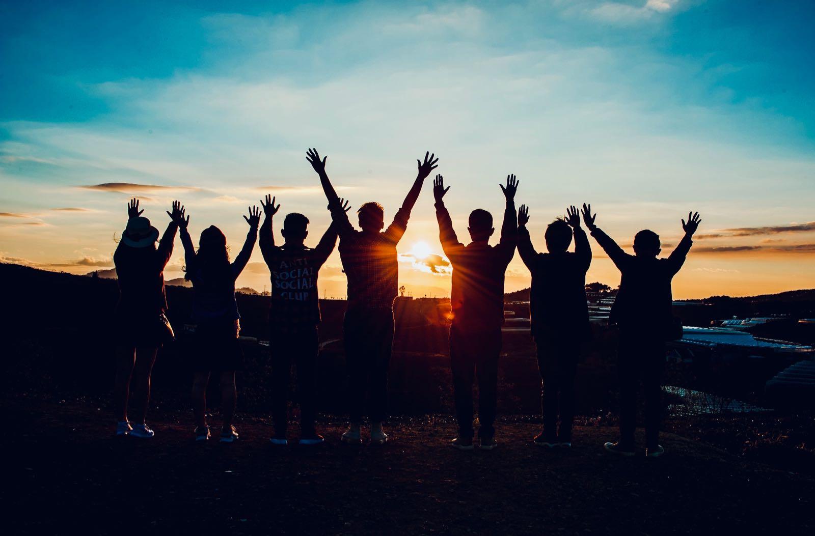 BILDBESCHREIBUNG: Gruppe junger Menschen beim Sonnenuntergang