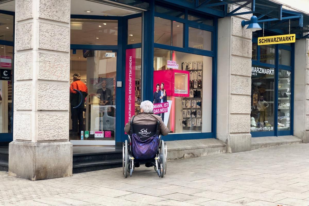 Person vor einer kleinen Treppe im Rollstuhl